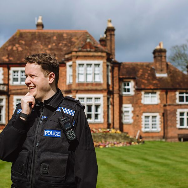 Community officer in front of brick building