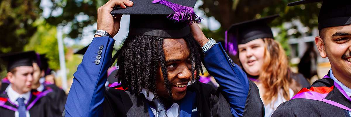 Male student with dreadlocks in graduation robes and hat