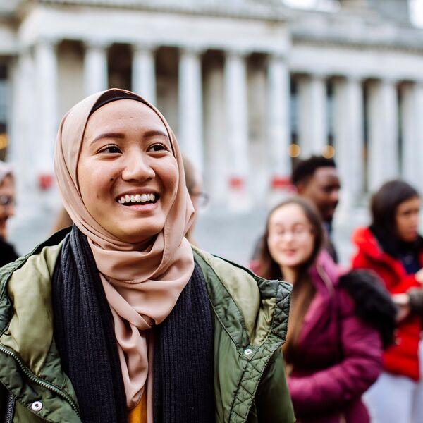 International students smiling and laughing outside Portsmouth Guildhall