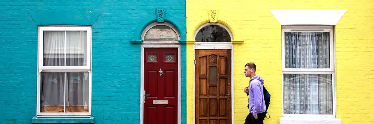 Male student outside bright coloured houses