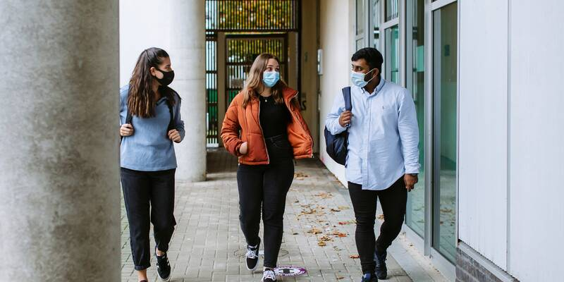 Three people walking along wearing masks