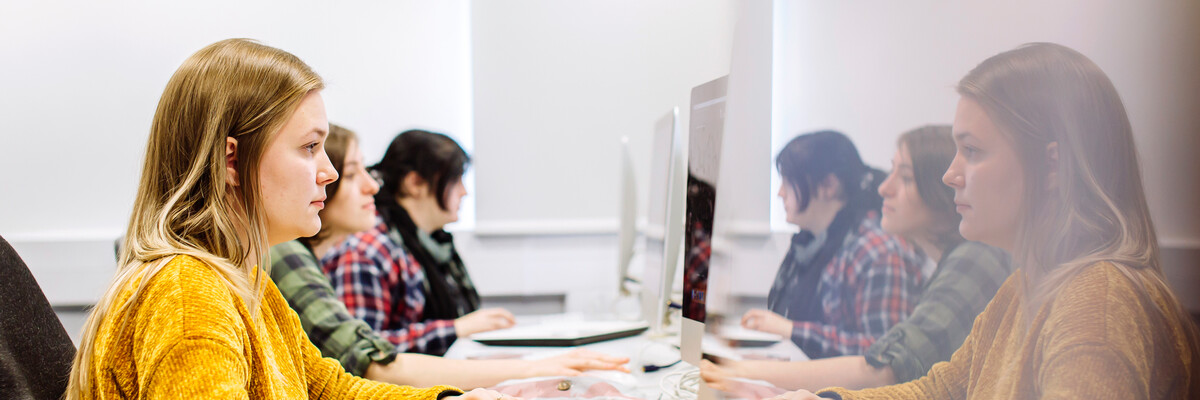 Female student in yellow jumper working in computer suite