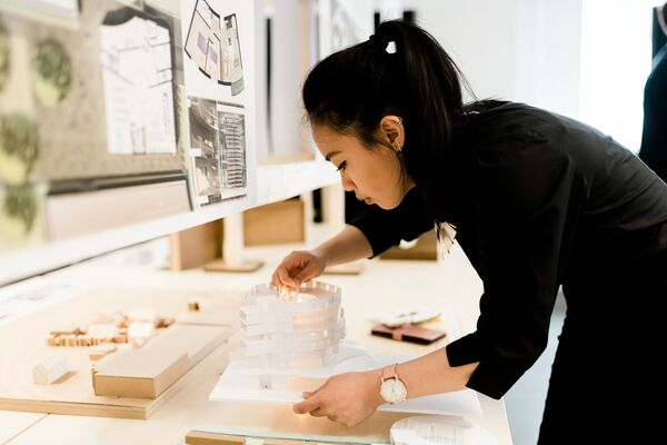 Female international architecture student building a model