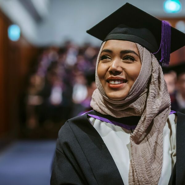 Female graduate in hijab walks during July 2019 graduation