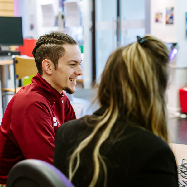 Smiling student getting advice for finding part time work from a careers adviser