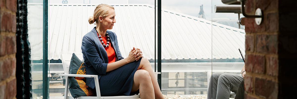 Woman wearing smart clothing sat crossed leg looking at an interviewer that is hidden by the brick wall