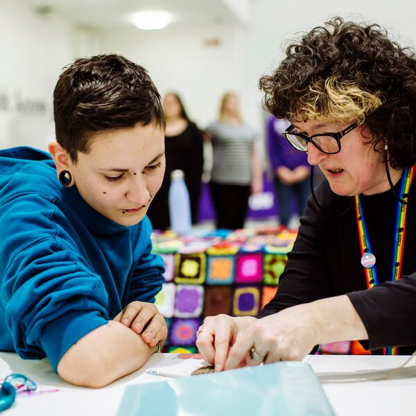 Staff member helping student crochet at feel good festival