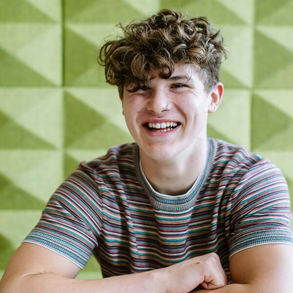 Student with curly hair smiling in front of green background