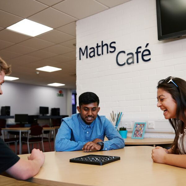 Students sat around table in the Maths Cafe playing a game