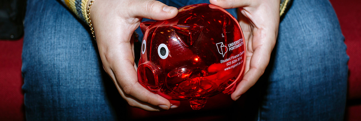 Student holding red University of Portsmouth piggy bank