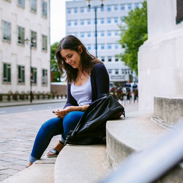 Student using mobile phone while sitting on steps outside the Park building