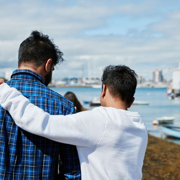 student with arm around his friend while walking along the Hard seafront