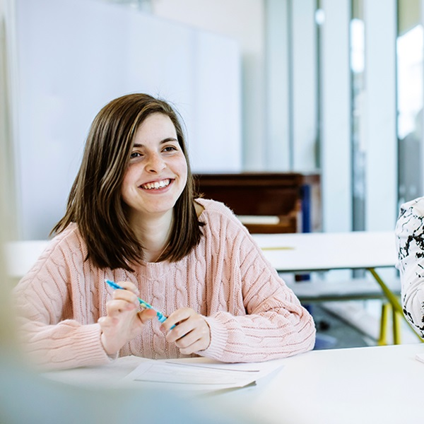 Male and female student smile and study at table