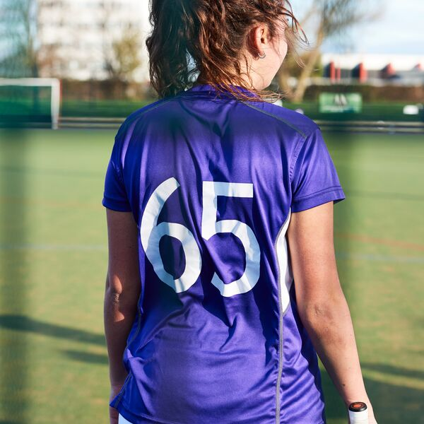 Female athlete in purple jersey stands facing pitch