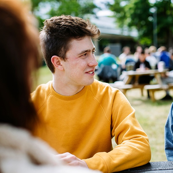 Students chatting at a picnic bench in the park, one wearing a yellow jumper and the other a denim jacket