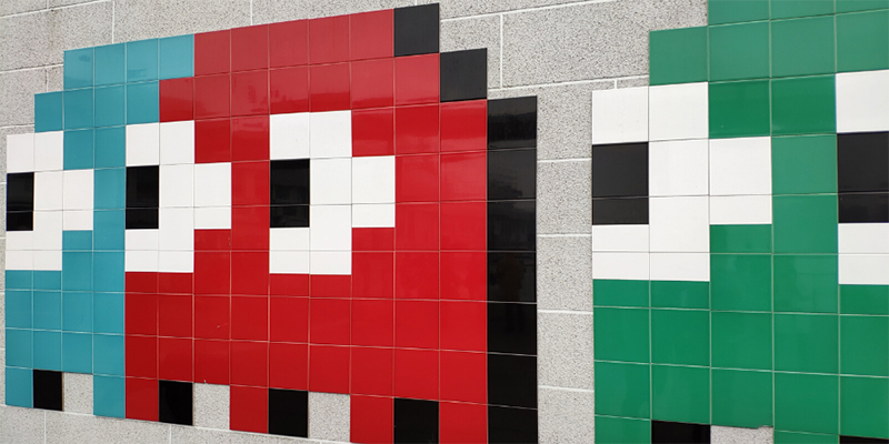 Blue, red, and green pacman ghosts on a tile wall