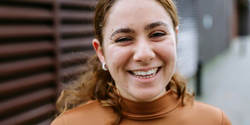 Close up of Stavroulla who is smiling and wearing brown top