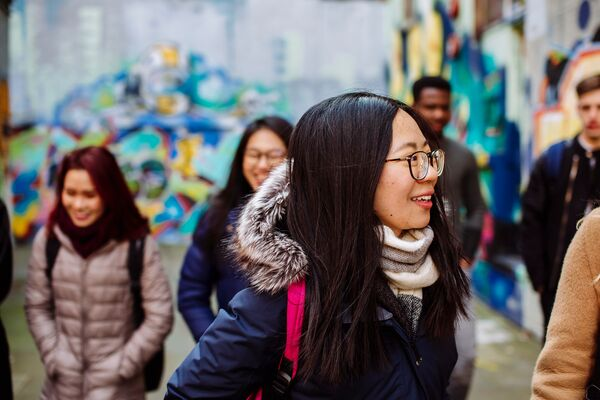 Group of international students walk in front of street art