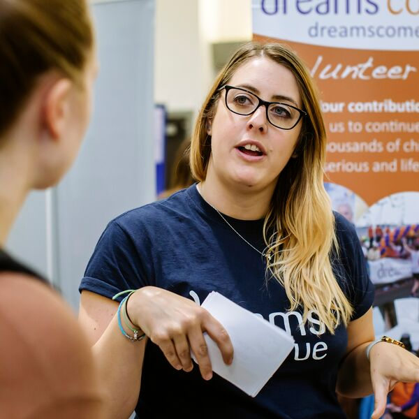 Woman speaking to student at volunteering fair