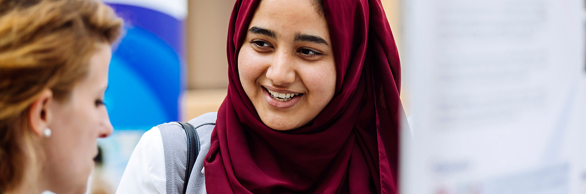 Student in hijab has a conversation with peer at research conference